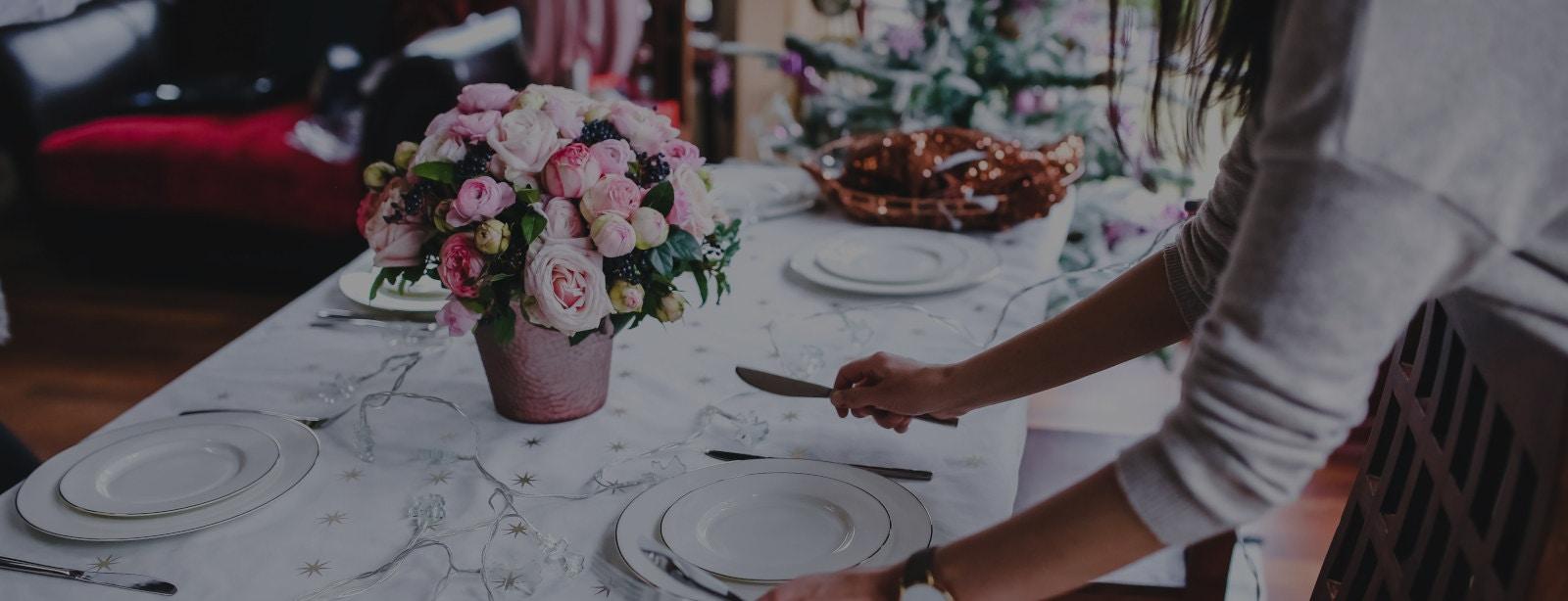 Dienstleisterin deckt Hochzeitstisch mit Dekoverleih