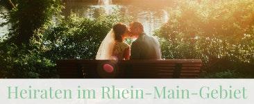 Heiraten im Rhein Main Gebiet: Brautpaar küsst sich auf einer Parkbank