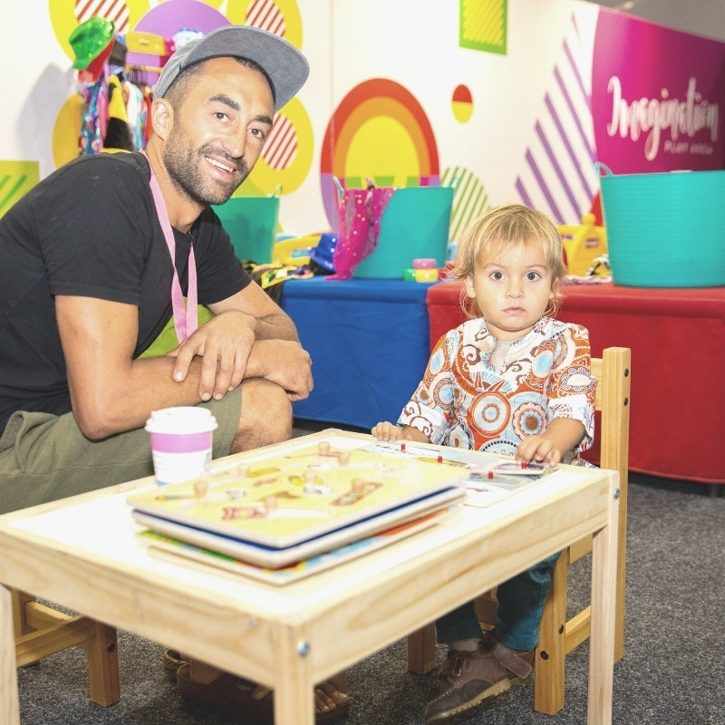 Image of a dad and his child sitting at a kids table with text underneath that reads Imagination Play Our colourful and inviting imagination play area offers kids a chance to create, play, discover… and the adults to have a break!