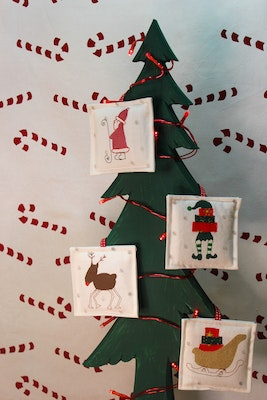 Julevidge Christmas hanging decorations, handmade and hand printed finished with free motion embroidery. Includes Santa, elf, reindeer and a sleigh.