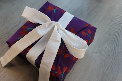 Julevidge Boomerang reusable fabric gift wrap with a bud and flower design and attached ribbons