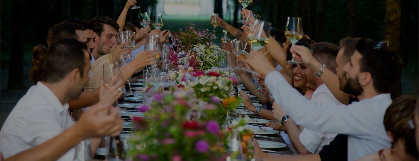 Freunde sitzen an einer langen Tafel und prosten sich mit Wein zu
