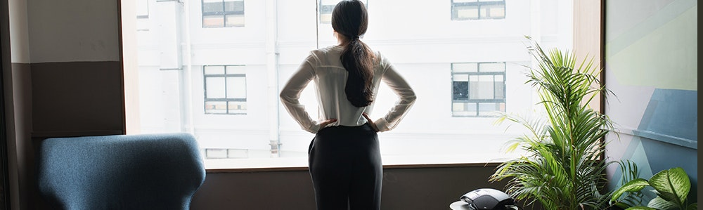 female-executive-looks-out-modern-office-window-jpg