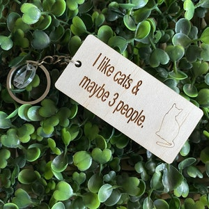 """""""I like cats & maybe 3 people"""" Quirky Timber Keyring - Laser Cut & Etched on Timber with Silvertone Hardware finished with a LLL Logo Tag."""