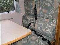 Lap and sash seatbelts. The table top is stowed for travel when the seats are used