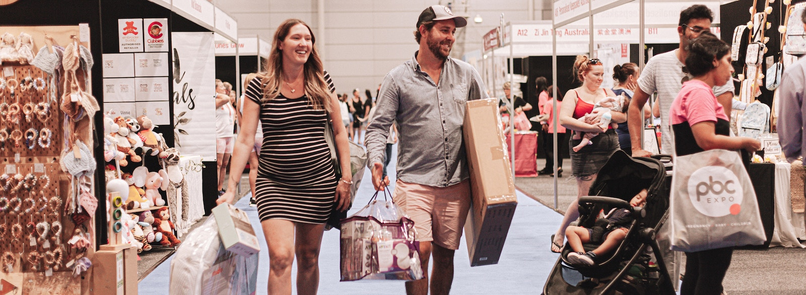 Woman and Man walking the expo floor holding products they have bought