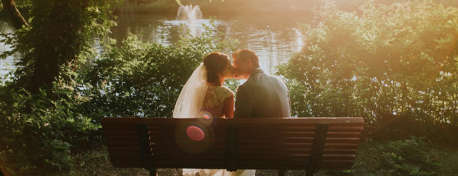 Brautpaar in Brautkleid und Anzug, küssend auf einer Parkbank in einem Park vor einem See