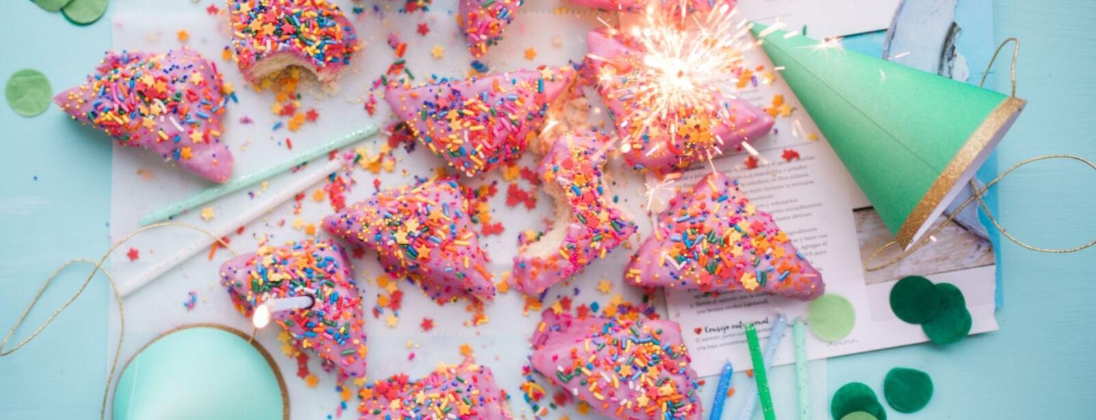 Partyhüte und rosa Kekse
