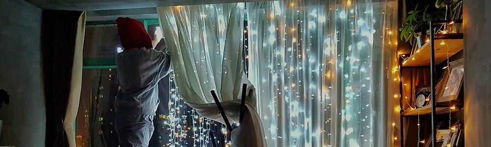 adult-installing-fairy-lights-on-bedroom-window-jpg