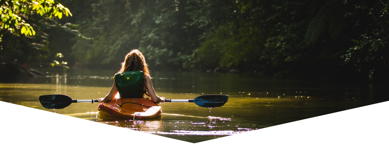 Woman kayaking on a small river or creek