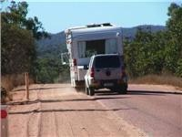 Motorhome and shopping cart struggle up hill Gregory Hwy