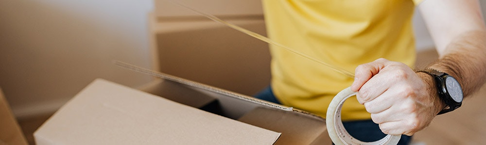 man-packing-boxes with sticky-tape-in-hand