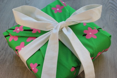 Julevidge Boomerang reusable fabric gift wrap with a cherry blossom design and attached ribbons