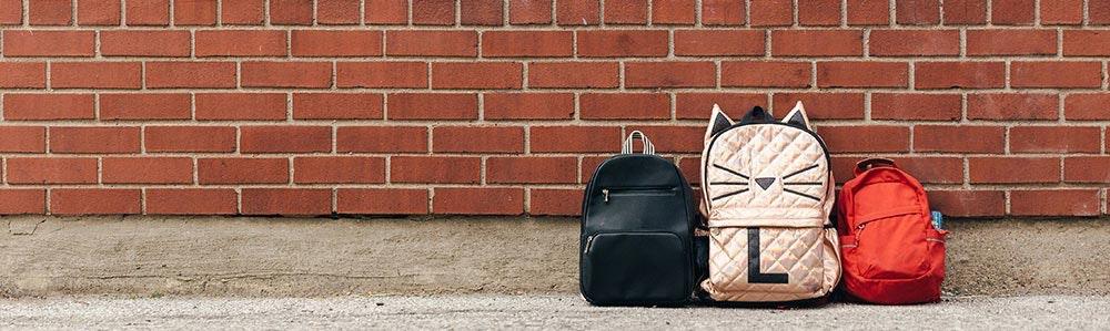 three-childrens-backpacks-brick-negative-space-jpg